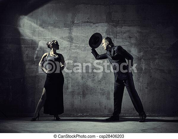 Man and woman dancers, concrete building surroundings