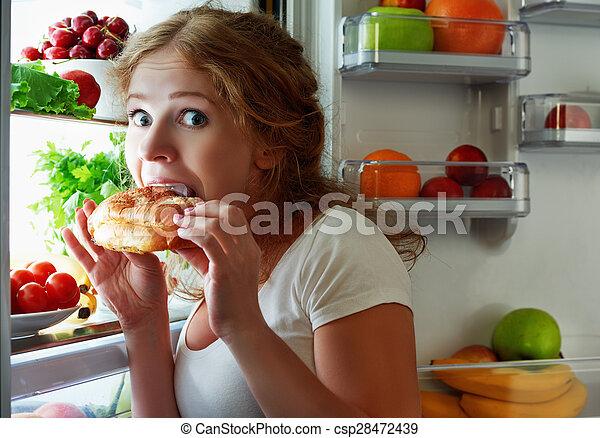 Woman eats night stole the refrigerator