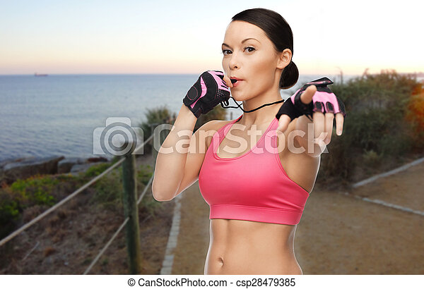 woman coach blowing whistle over beach background