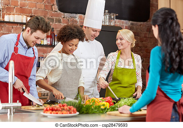 happy friends and chef cook cooking in kitchen
