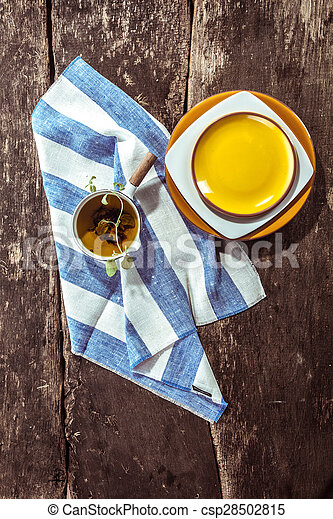 Directly overhead view of small pot with handle, blue and white striped teatowel and yellow and white stacked plates on rustic distressed wooden table