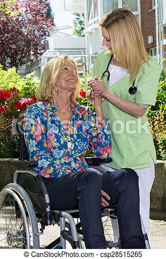 Nurse Holding Hands with Senior Woman in Garden