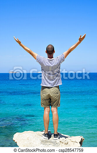 man with his arms in the air in front of the ocean