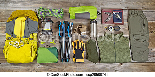 High angled view of organized hiking gear placed on rustic wooden boards in rectangle format.