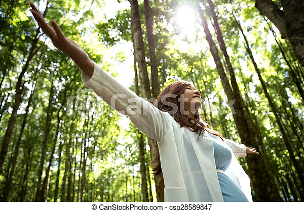 Pregnant young woman enjoying the forest with open arms