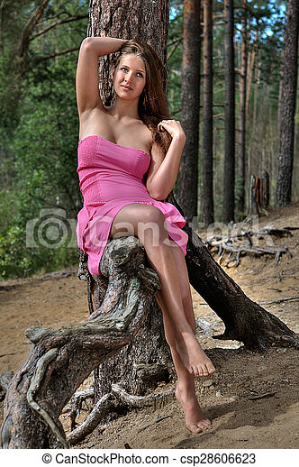 Young teen girl is resting in a forest, in countryside.