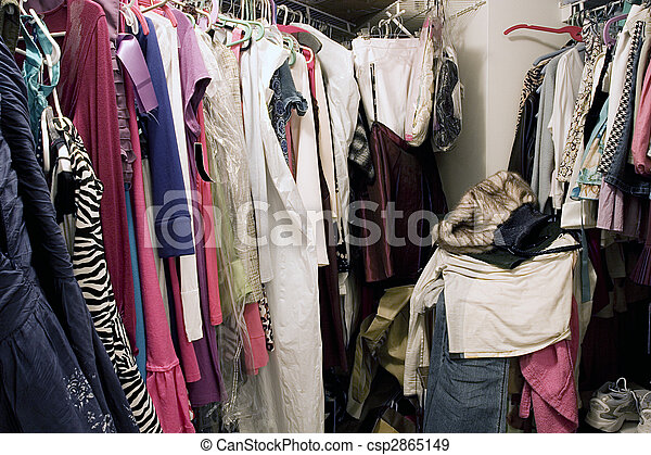 Messy unorganized closet full of hanging clothes - csp2865149