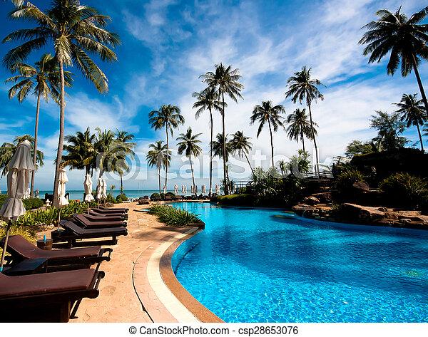 Deckchairs in tropical resort hotel pool