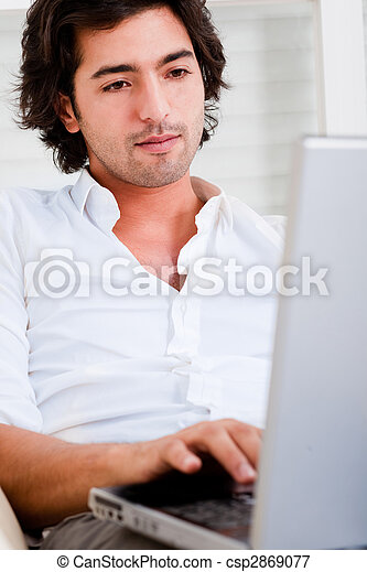 Attractive young man browsing the internet  - csp2869077
