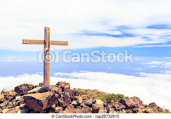 Christian cross on mountain top, rocky summit, beautiful inspirational landscape with ocean, island, clouds and blue sky, looking at scenic blue sea and white clouds.