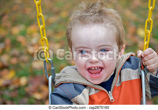 Cute toddler laughing while grasping onto the chains of a swing at a playground. - csp2875160
