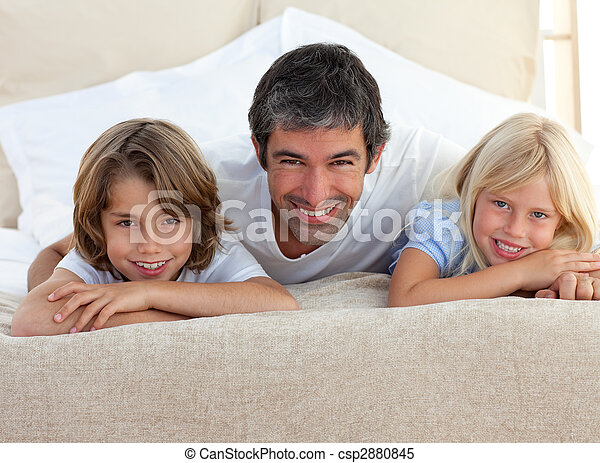 Caring father and his children lying on a bed - csp2880845