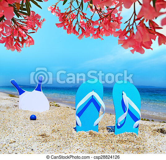 sandals and beach rackets under pink flowers - csp28824126