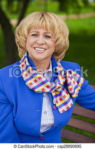Portrait of an elderly beautiful woman in blue jacket