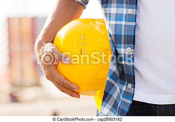 close up of builder hand holding hardhat outdoors