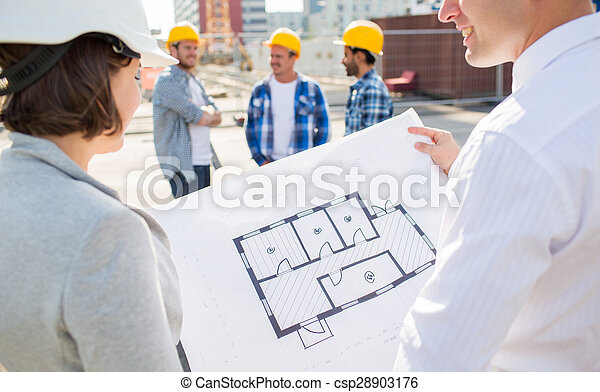close up of architects with blueprint at building