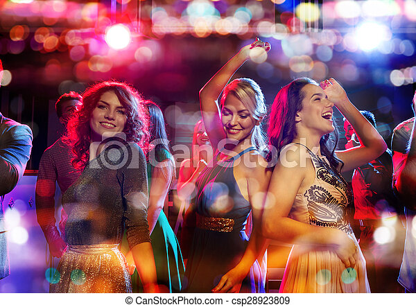 happy friends dancing in club with holidays lights