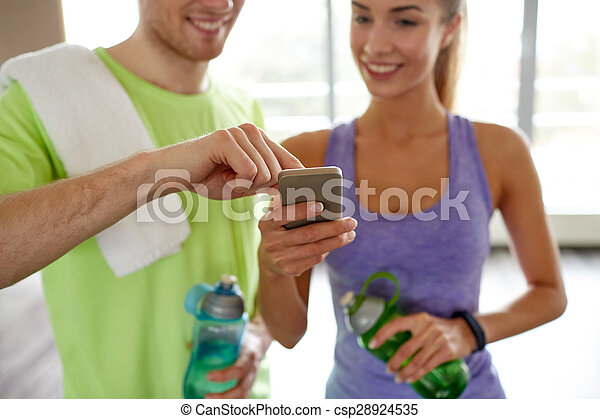 happy woman and trainer showing smartphone in gym