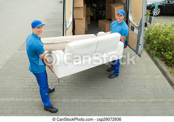 Workers Putting Furniture And Boxes In Truck