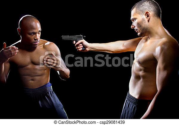 Martial artist disarming a criminal with a gun or close quarter combat