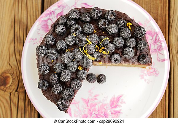 Delicious chocolate pie with fresh blackberries, icing sugar and lemon peel missing one piece on wooden table