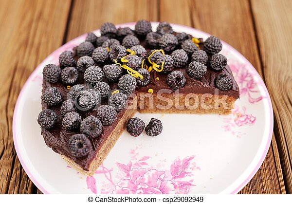 Delicious homemade chocolate pie with fresh blackberries, icing sugar and lemon peel missing one piece on wooden table
