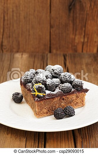 Piece of delicious homemade chocolate pie with ganache, fresh blackberries and lemon peel decorated with icing sugar in white plate on wooden table