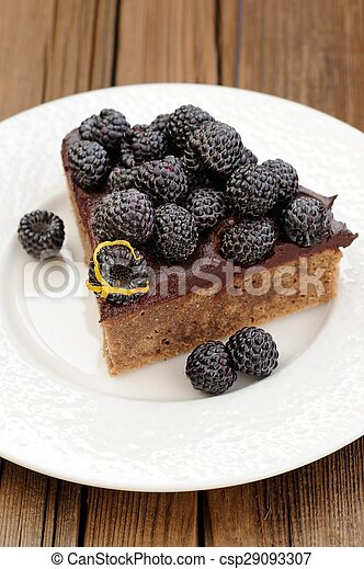 Piece of tasty chocolate pie with ganache, decorated with fresh blackberries, lemon peel and icing sugar in white plate on wooden table
