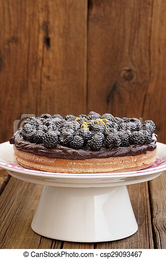 Tasty homemade chocolate pie with ganache, decorated with many fresh blackberries, lemon peel and icing sugar in white pedestal on wooden table