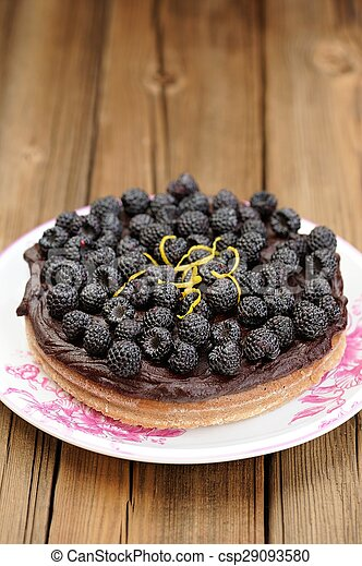 Fresh homemade chocolate pie with ganache, decorated with fresh blackberries, lemon peel and icing sugar in white plate on wooden table