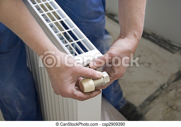 hands of a plumber installing a connection at a radiator - csp2909390