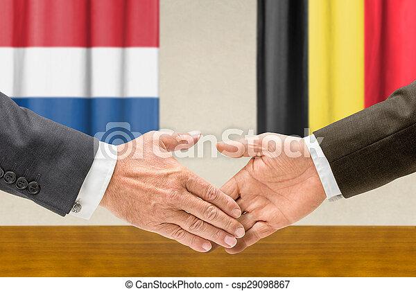 Representatives of the Netherlands and Belgium shake hands