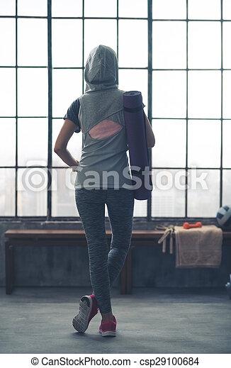 Woman standing relaxing in gym seen from behind wearing hoodie
