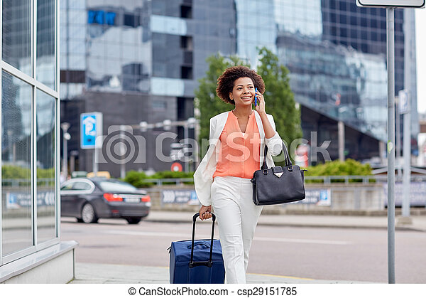 happy woman with travel bag calling on smartphone