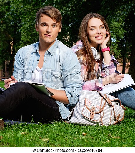 Students couple preparing for final exams in a city park