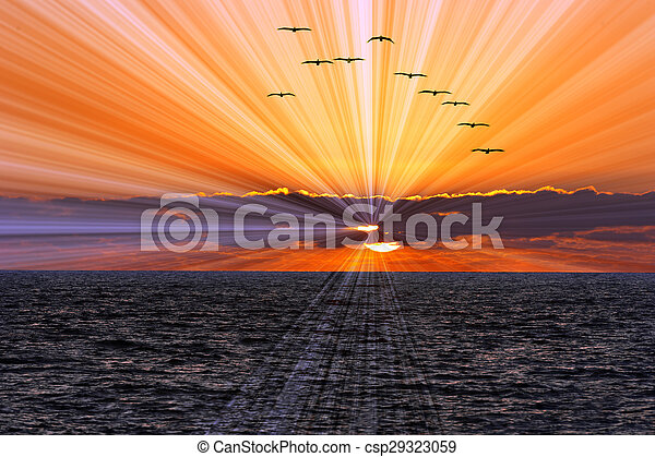 Ocean sunset sun rays is a flock of birds flying overhead while a brilliant burst of sun rays shoot out from behind the clouds and the sun sets on the calm blue ocean waves.