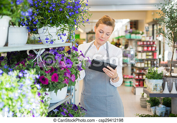 Florist Using Digital Tablet In Flower Shop