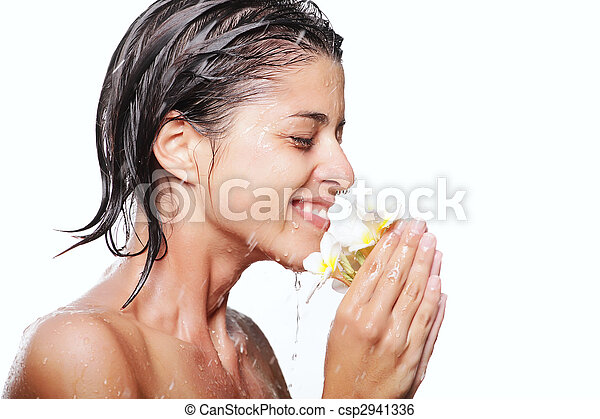 Young beautiful woman taking a shower and holding exotic flowers. Isolated over white background. - csp2941336