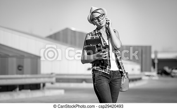stylish woman with notebooks and papers posing on street