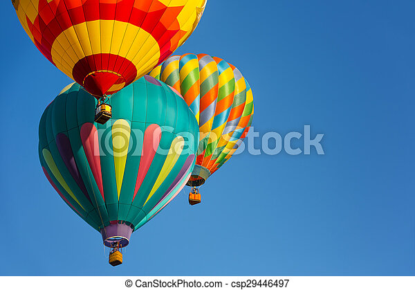 Group of hot air balloons against blue sky.
