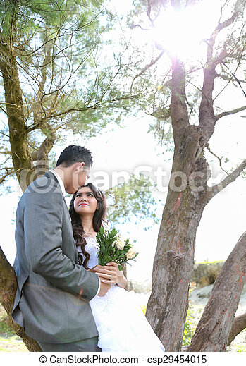 newlywed couple lean back on tree in sunny day