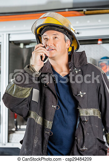 Mature Fireman Using Walkie Talkie At Fire Station