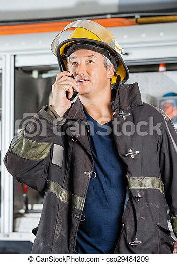 Mature Fireman Using Walkie Talkie At Fire Station