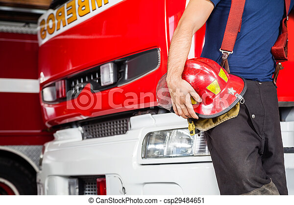 Fireman Holding Red Helmet While Leaning On Truck