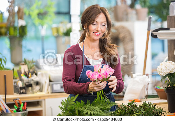 Florist Making Bouquet Of Pink Roses In Shop