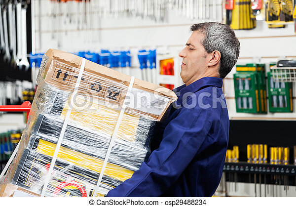 Worker Lifting Heavy Tool Package In Hardware Shop