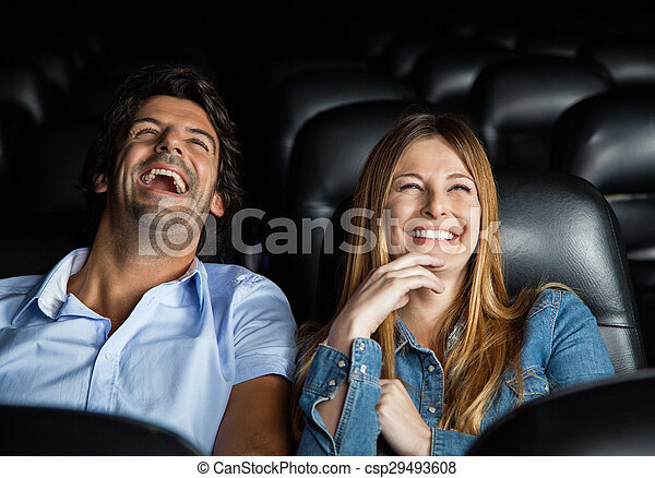 Couple Laughing While Watching Film In Theater - csp29493608