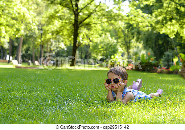 Cute little toddler girl laying in the grass on a sunny summer day - csp29515142