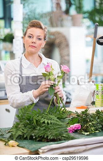Florist Making Rose Bouquet In Flower Shop