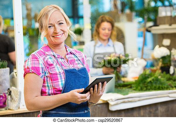 Smiling Female Florist Holding Digital Tablet In Flower Shop
